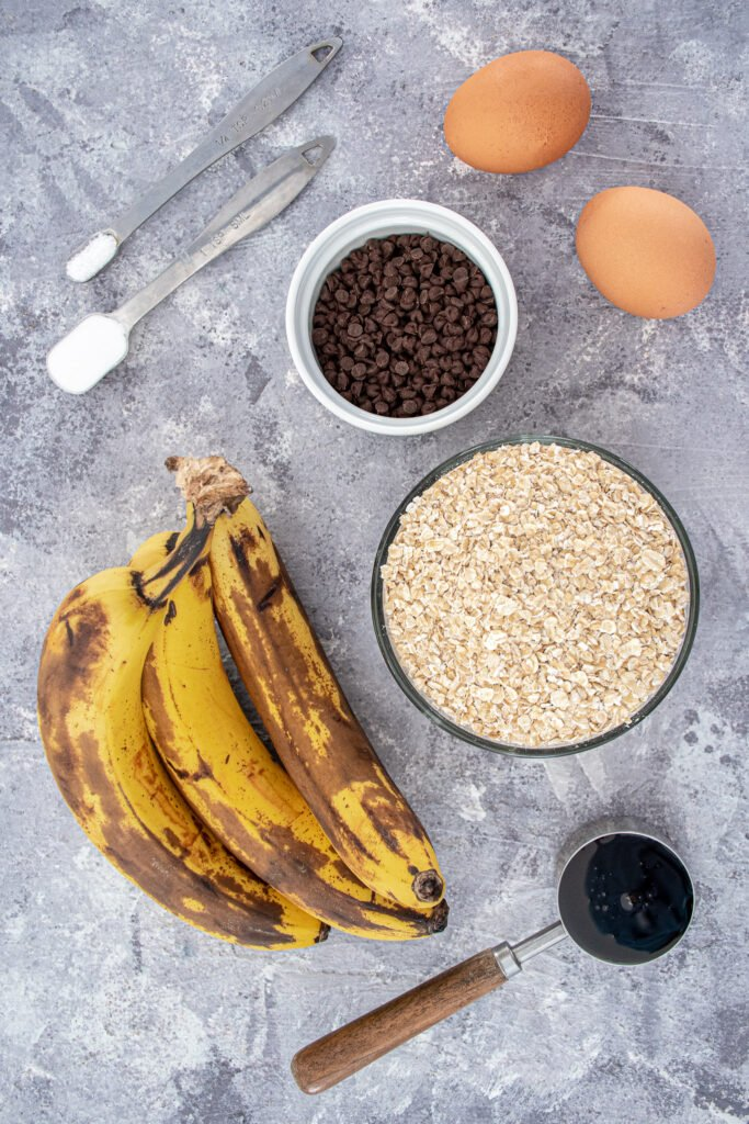 Ingredients for flourless banana muffins showing off bananas, oats, eggs, and mini chocolate chips as a few of the ingredients.