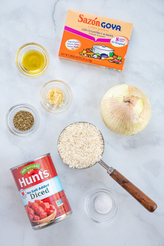 Ingredients needed to make mexican rice arranged on a table top including Sazón Goya Con Cilantro Y Achiote.