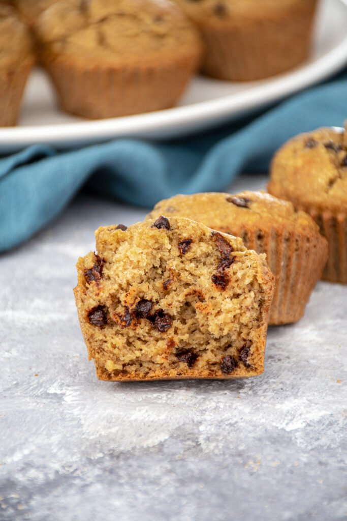Inside of a flourless blender bababan muffin showing off a fluffy and tender inside with mini chocolate chips.