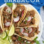 Pinterest Pin with text overlay 'Crockpot Barbacoa', image of plate with a bunch of tacos filled with barbacoa and garnished with cilantro.