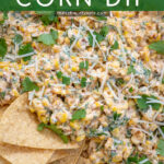Pinterest Pin with text 'Mexican Street Corn Dip', image of street corn dip in a white bowl with tortilla chips.