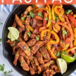Pinterest Pin with text 'Skillet Chicken Fajitas', image of a cast iron filled with chicken and brightly colored bell peppers.