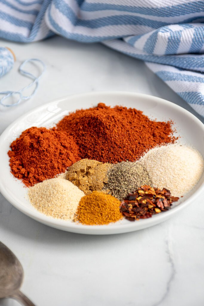 Small white plate with mounds of different colored spices.