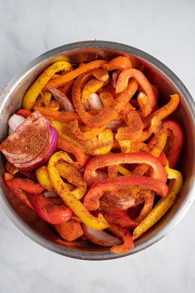 Colorful bell peppers and red onions in a bowl covered in fajita seasoning.