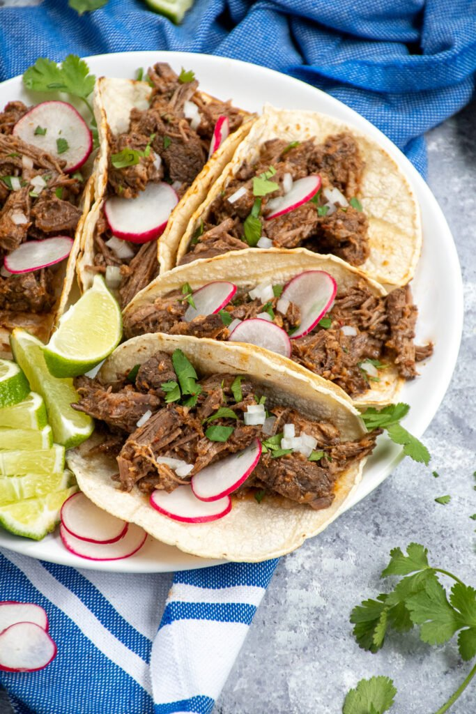 Side angle of a white plate filled with a bunch of tacos filled with crockpot barbacoa and garnished with onions, radishes, and cilantro.