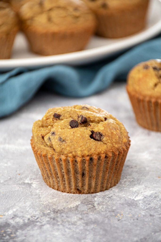 A single Flourless Banana Blender Muffin with mini chocolate chips sitting on a countertop with a plate of muffins sitting in the background.