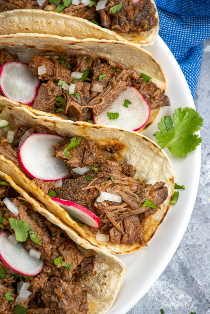 Close shot of a plate of tacos with beef barbacoa garnished with onions and cilantro.