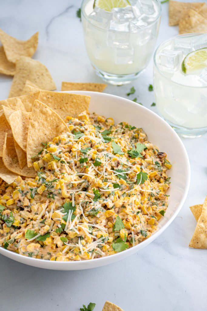 Angled view of a table with a bowl of street corn, tortilla chips, and margaritas.