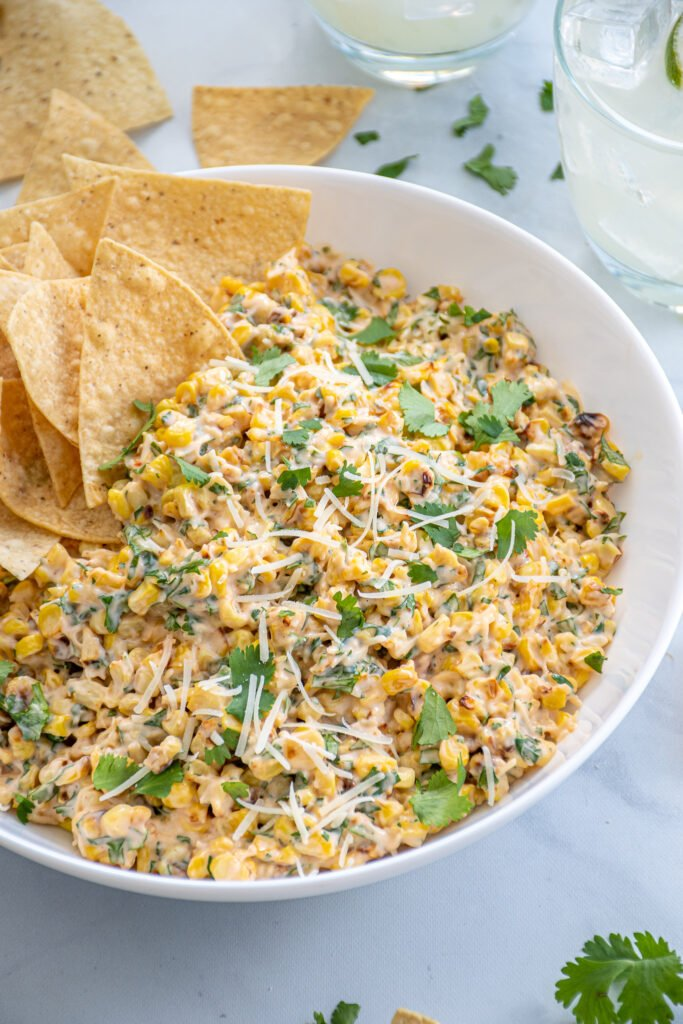 Mexican Street Corn Dip in a bowl garnished with parmesan cheese and cilantro with a handful of tortilla chips on the side.