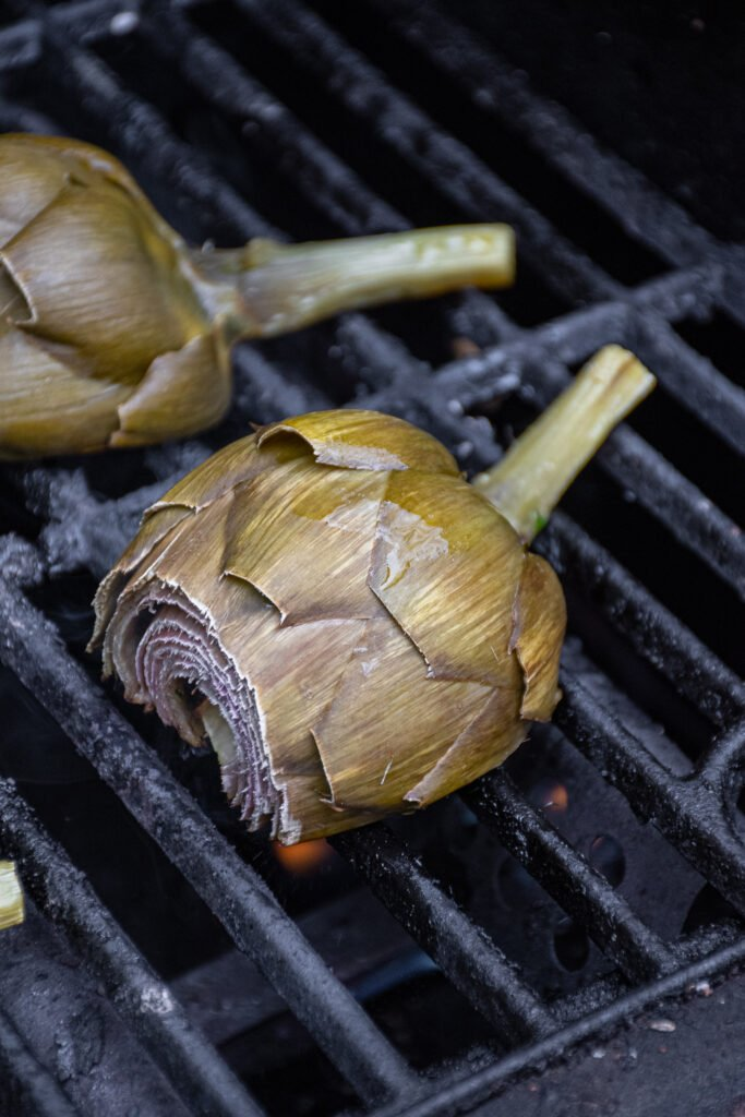 Close up of half an artichoke on a grill grate.