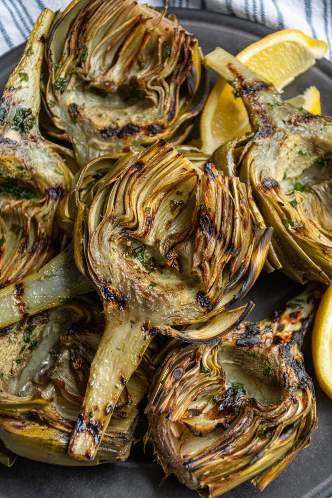 Close up of a platter full of grilled artichokes, close up on a single artichoke with grill marks on it.