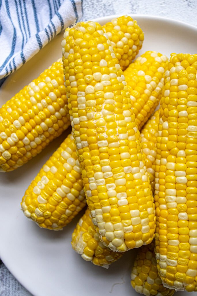 Close up of an ear of corn on a plate, melted butter is in between the bright yellow kernels.