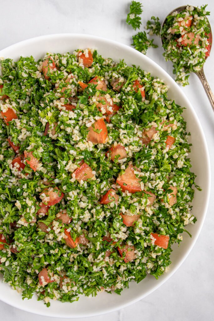 Close up view of tabbouleh salad recipe in a bowl showing off parsley, tomatoes, and bulgur.