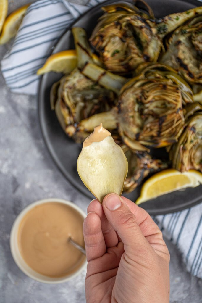 A leaf from an artichoke dipped into the creamy balsamic dipping sauce.