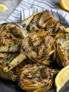 A platter of grilled artichokes with a half of an artichoke on top showing off charred grill marks.