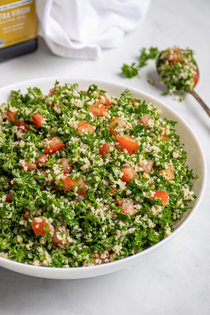 A large white bowl filled with tabbouleh salad with a spoonful out on the side with parsley leaves falling off.