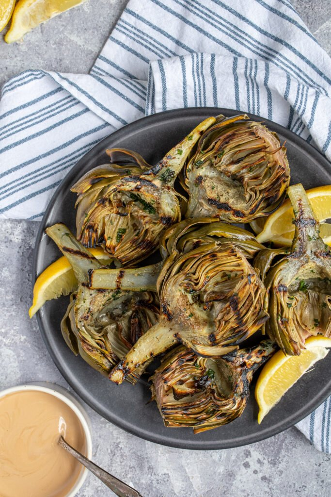 Overhead view of a platter of grilled artichokes fresh from the grill surrounded by cut up lemons and balsamic dipping sauce.