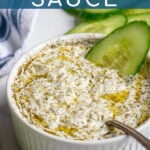Pinterest Pin with text overlay 'Tzatziki Sauce', image of small white bowl filled with homemade tzatziki sauce.