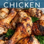 Pinterest Pin with text 'Greek Marinated Grilled Chicken', image of a plate piled high with golden brown grilled chicken legs.