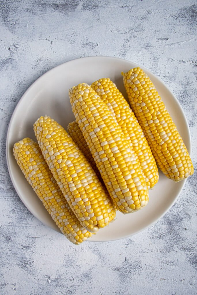 White plate full of a stack of raw sweet corn on the cob.