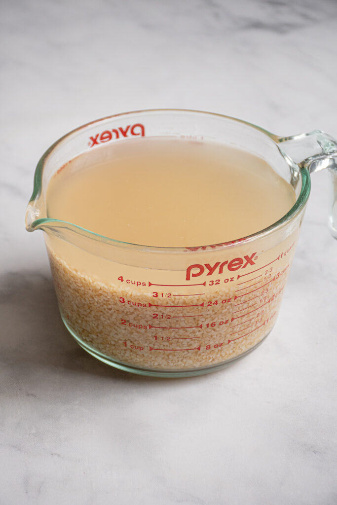 Large glass measuring cup filled with soaking bulgur and water.