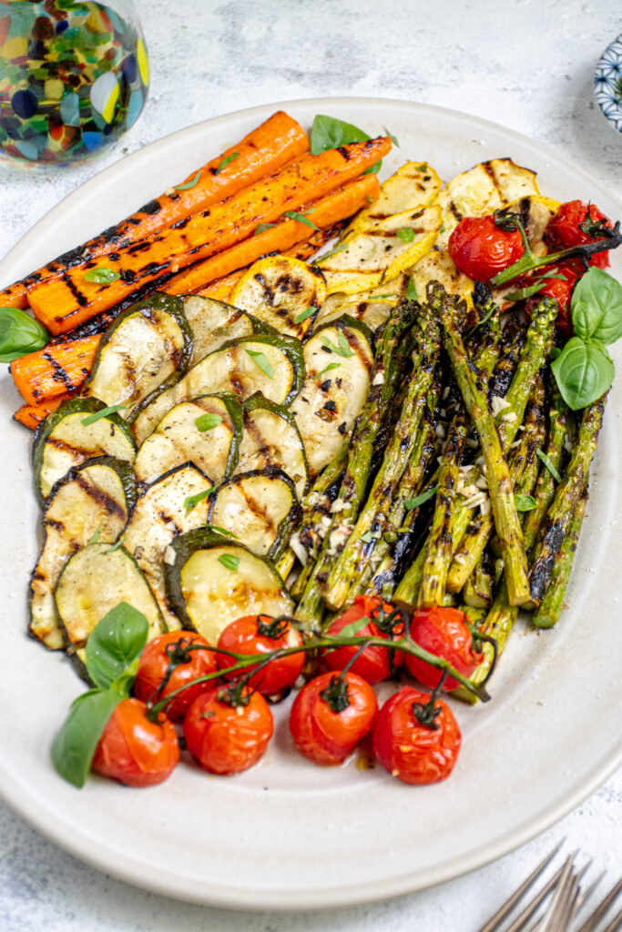 Angled view of a white platter filled with marinated and grilled vegetables including zucchini, asparagus, and tomatoes.