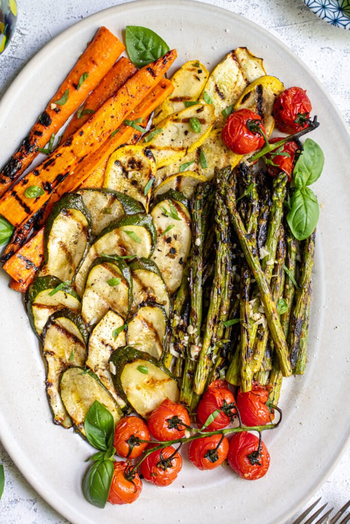 Close up of marinated grilled veggies on a platter covered in fresh basil.