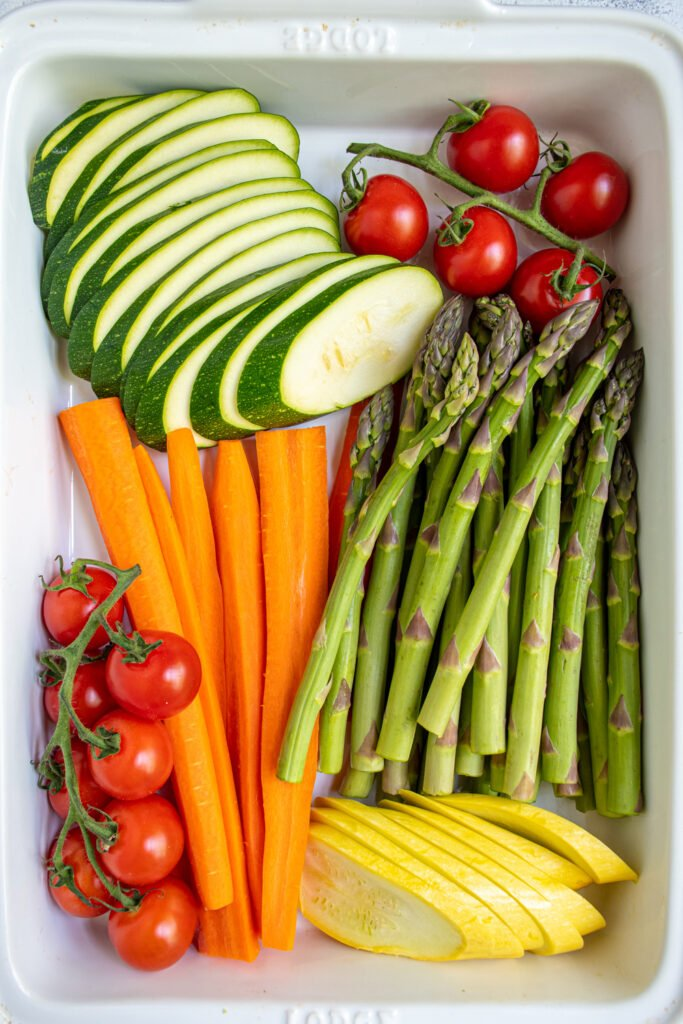 Cut vegetables placed nicely in a white baking dish.