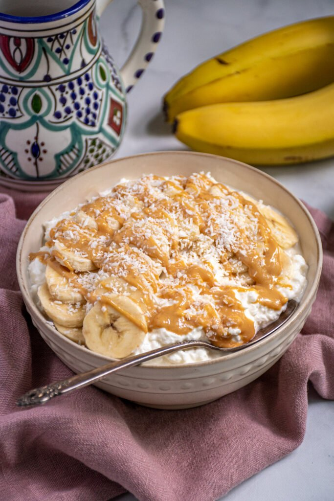 White bowl gilled with cottage cheese and topped with banana slices, peanut butter, and shredded coconut.