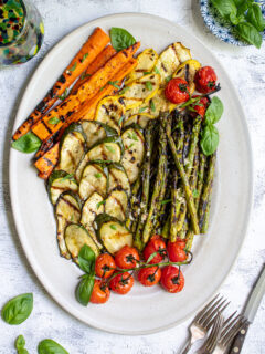 Overhead view of a white platter filled with marinated grilled veggies including zucchini, asparagus, carrots, and tomatoes.