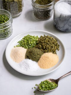 On a small white plate is little piles of 6 different spices that make up DIY Ranch Seasoning Mix.
