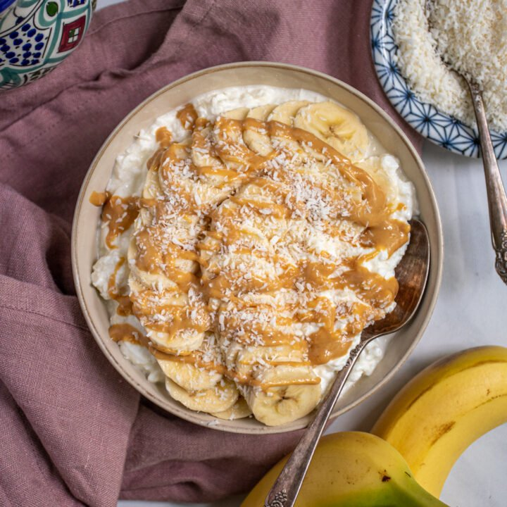 Overhead view of a bowl with a spoon filled with cottage cheese and topped with banana slices, drizzled peanut butter, and shredded coconut.