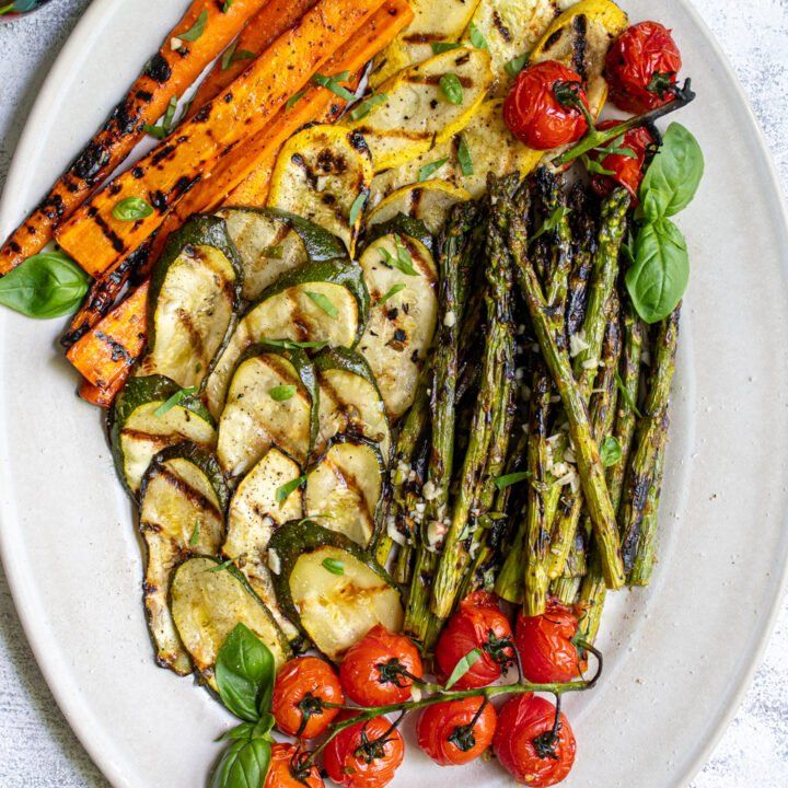 Marinated and grilled zucchini, asparagus, carrots, and tomatoes on a platter covered in fresh basil leaves.