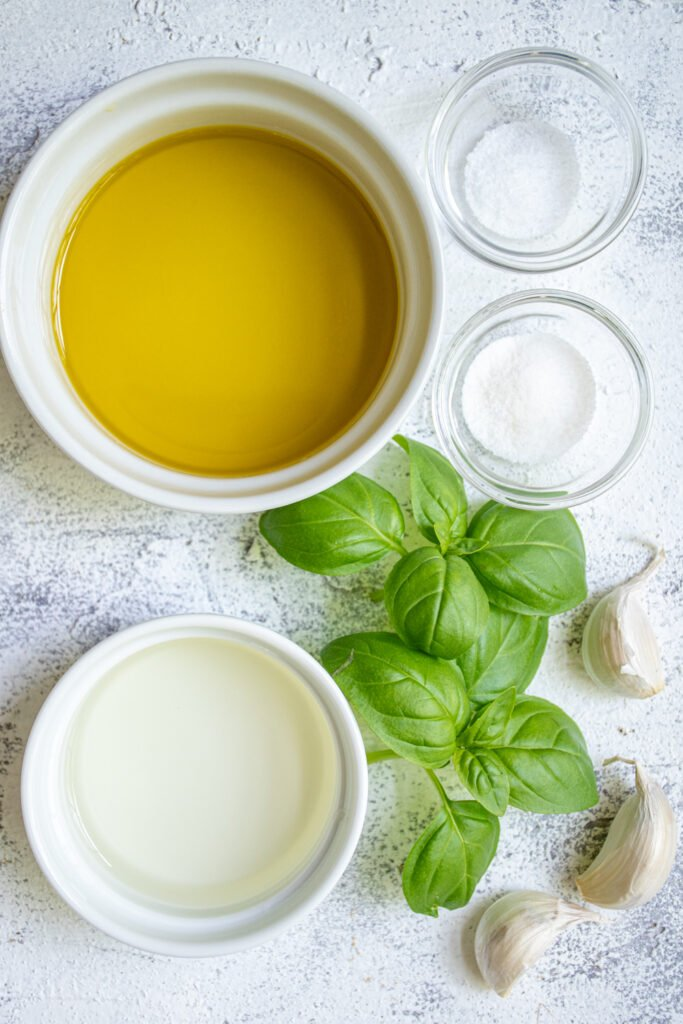 Ingredients needed to make a marinade for grilled vegetables including olive oil, garlic, and fresh basil.