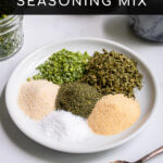 Pinterest Pin with text 'Homemade Ranch Seasoning Mix', image of a small white plate with piles of 6 different spices needed to make ranch.