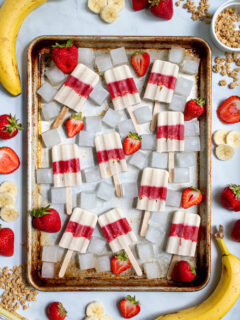 Sheet tray full of red and white parfait popsicles and ice cubes surrounded bu sliced strawberries, bananas, and bits of granola.