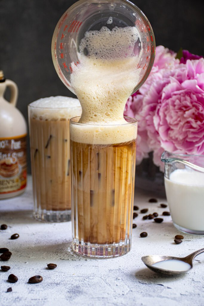 Salted Maple Foam being poured into a glass of cold brew coffee.