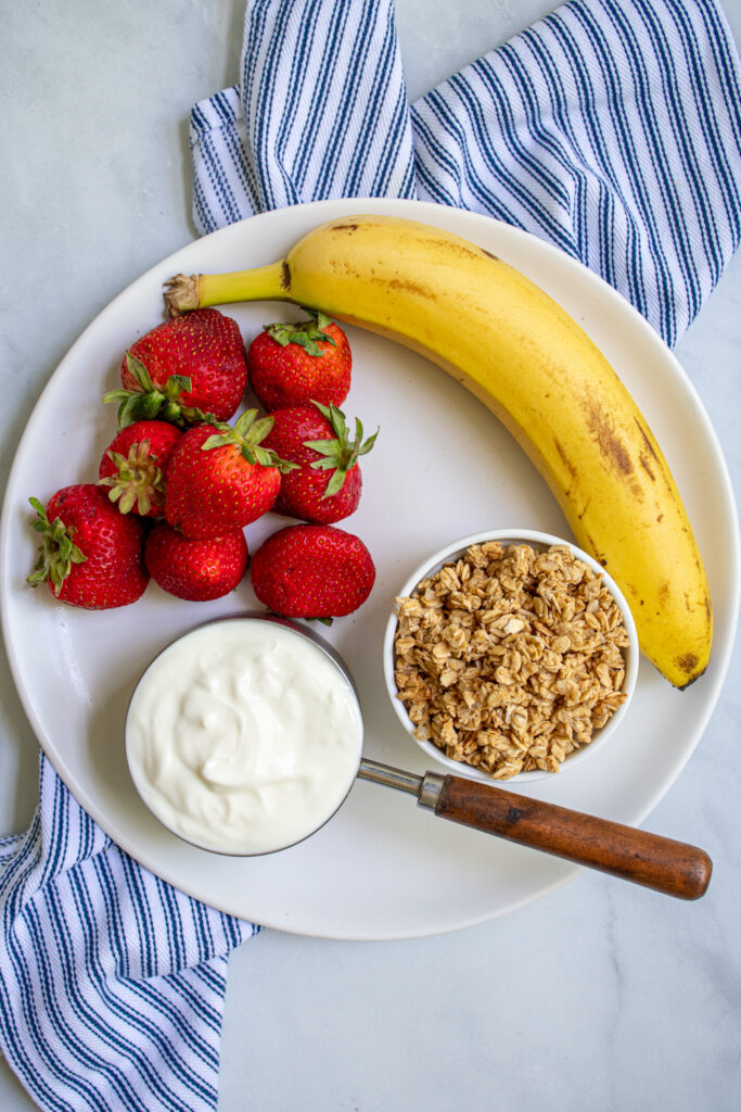 Ingredients to make parfait popsicles on a white plate including strawberries, a banana, yogurt, and granola.