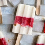 Pinterest Pin with text 'Healthy Parfait Breakfast Popsicles', image of a sheet tray filled with red and white layered popsicles.