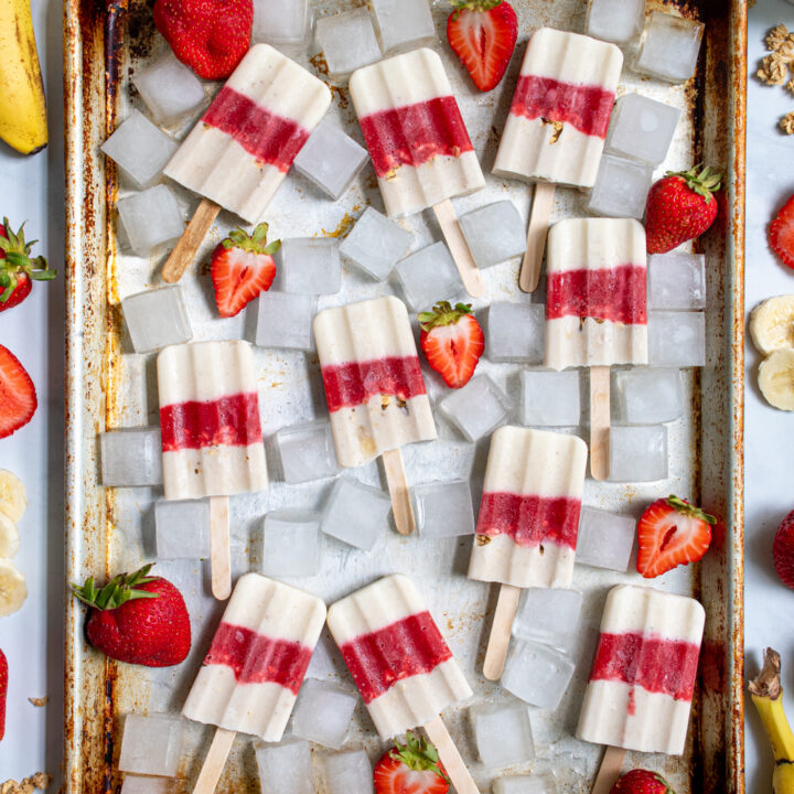 Overhead view of a sheet pan filled with red and white parfait breakfast popsicles surrounded by ice cubes and sliced strawberries.