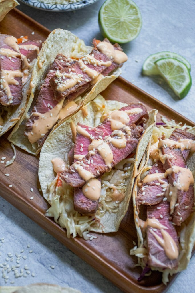 Angled view of the tuna steak tacos showing off the sliced tuna steak overtop a bed of coleslaw and topped with sriracha mayo and sesame seeds.