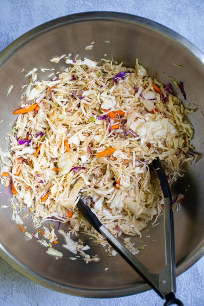 A large bowl filled with asian coleslaw ready to be used for the tuna steak tacos.