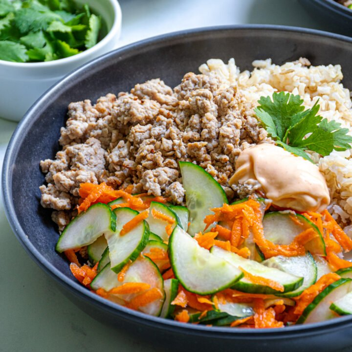 Close up of a bowl of brown rice, ground pork, and pickled vegetables topped with sriracha mayo.