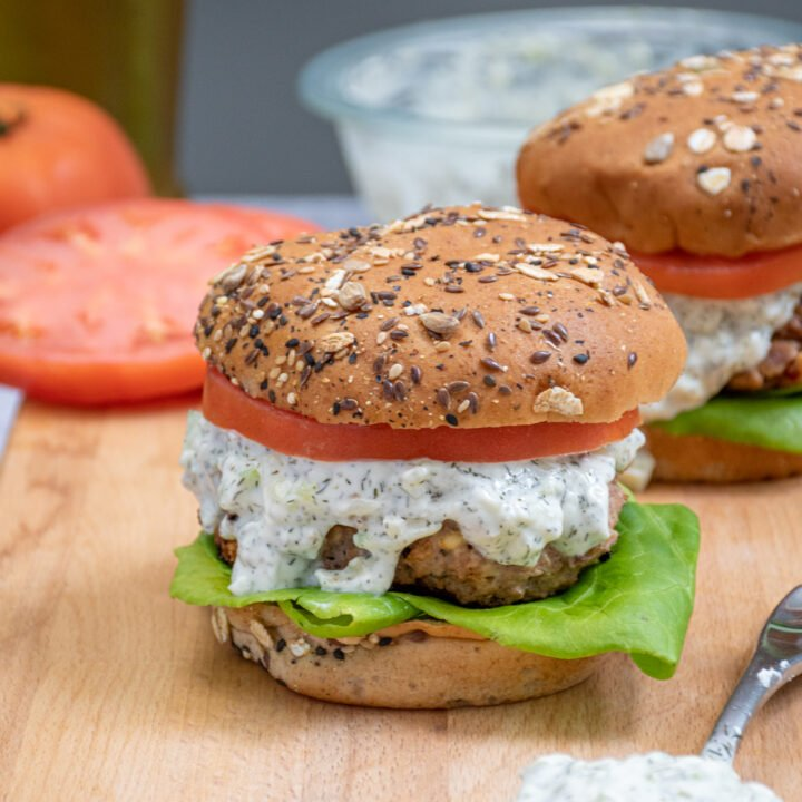 A greek turkey burger topped with tzatziki sauce, lettuce, and tomato sitting on a cutting board black next to a spoon of tzatziki.