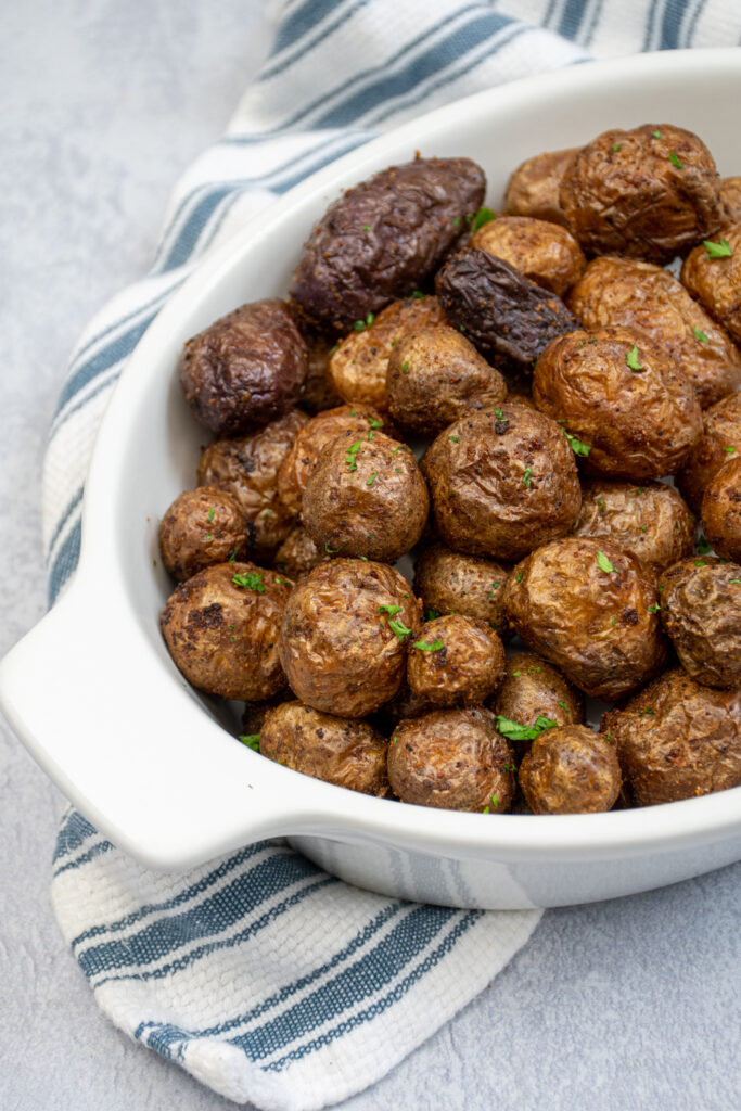 Air fryer baby potatoes in a white ceramic serving dish covered in salt and garnished with chopped parsley.