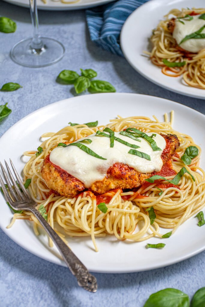 A white plate piled high with spaghetti topped with an Oven Baked Chicken Parmesan topped with melted mozzarella and garnished with pieces of fresh basil.