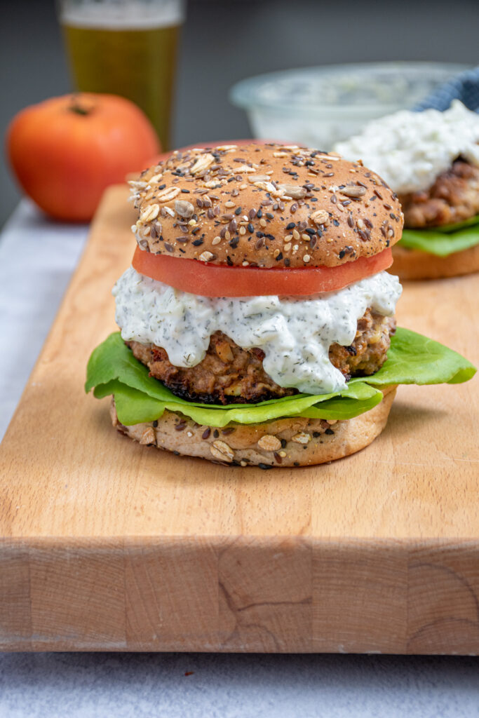 A Mediterranean Turkey Burger topped with Tzatziki sauce, tomatoes, and lettuce sitting on a butcher block next to another turkey burger.
