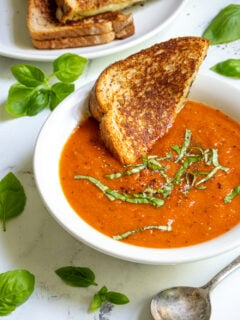 A white bowl filled with roasted red pepper and tomato soup garnished with fresh basil and a toasted grilled cheese being dunked into the soup.