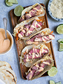 Five tuna steak tacos sitting on a string platter garnished with sriracha mayo and sesame seeds.