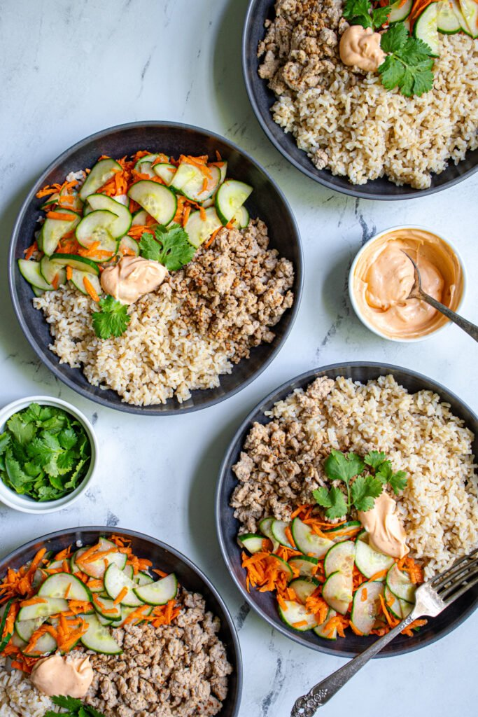 Overhead view of four black bowls filled with brown rice, ground pork, and quick pickled carrots and cucumbers.